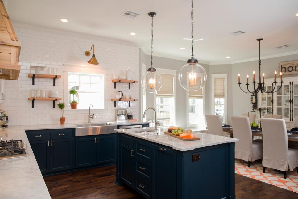 Several light fixtures highlight the wood and tile elements of this craftsman style kitchen as seen on Fixer Upper.