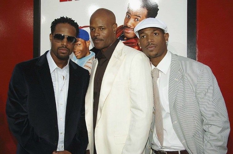 Actors and brothers Shawn Wayans, Keenen Ivory Wayans and Marlon Wayans in front of movie poster