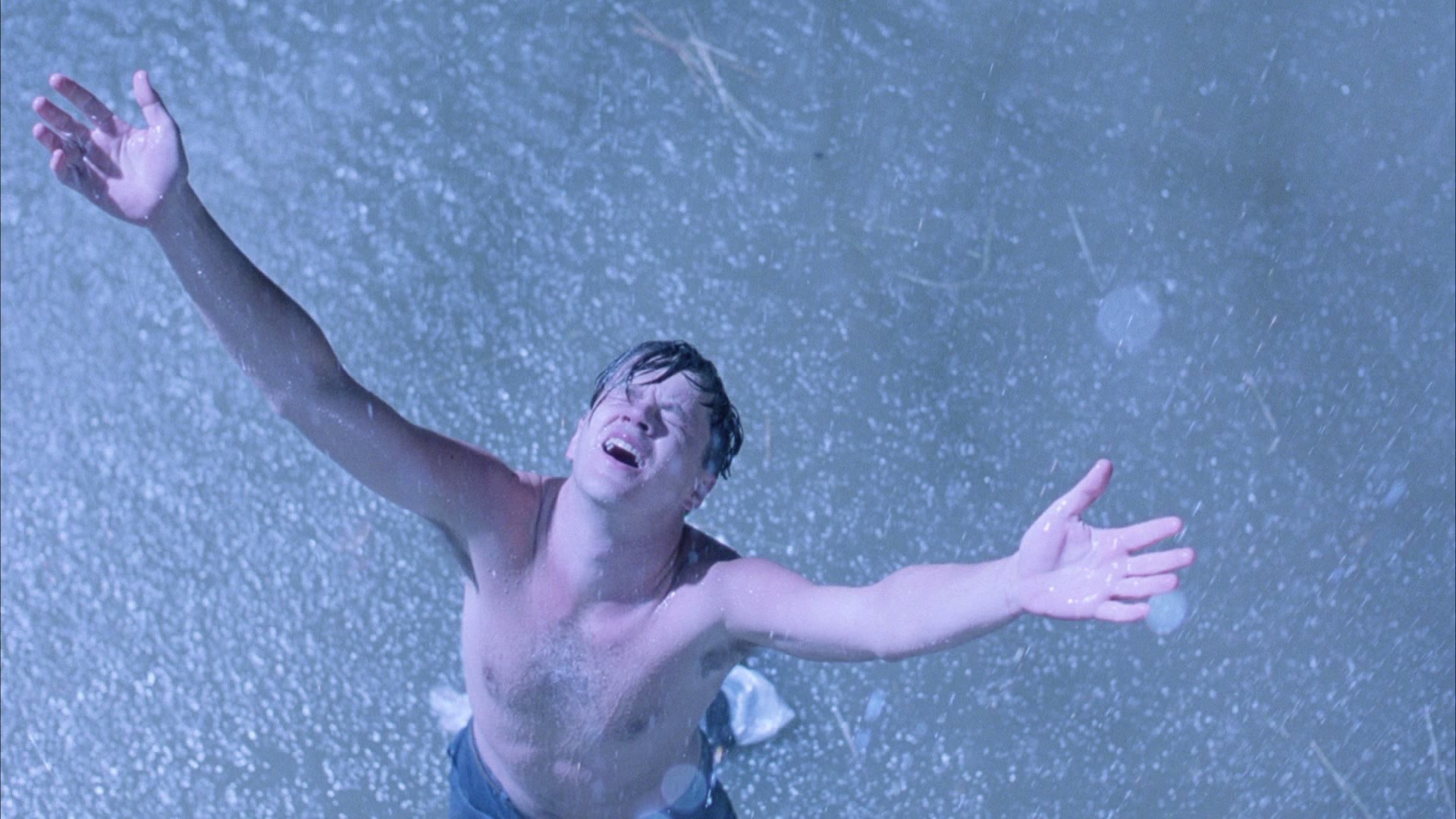 """Andy raises his arms to the sky in the movie """"The Shawshank Redemption"""""""