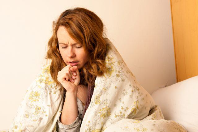 Sick woman coughing in bed under blanket.