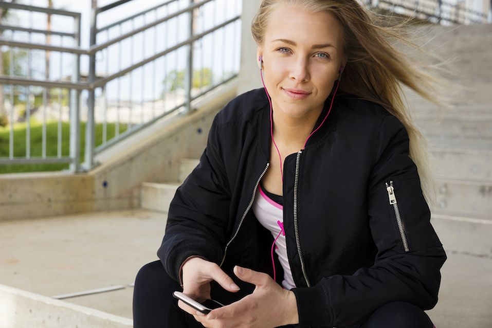 Smiling blonde woman sits outdoor