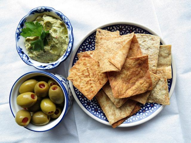 Hummus with green olives and pita chips on a table.