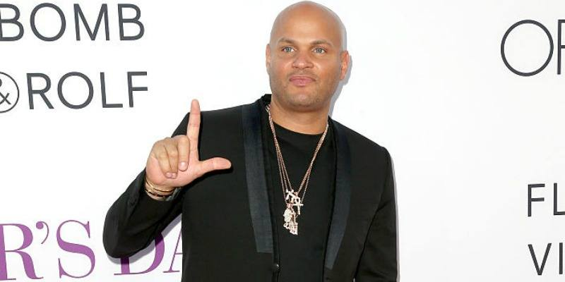 """Stephen Belafonte has his thumb and finger up in an """"L"""" shape on the red carpet."""