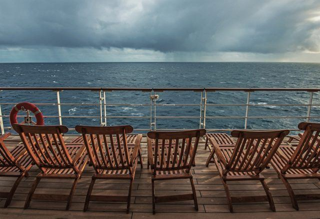 ship deck looking out at storm over water