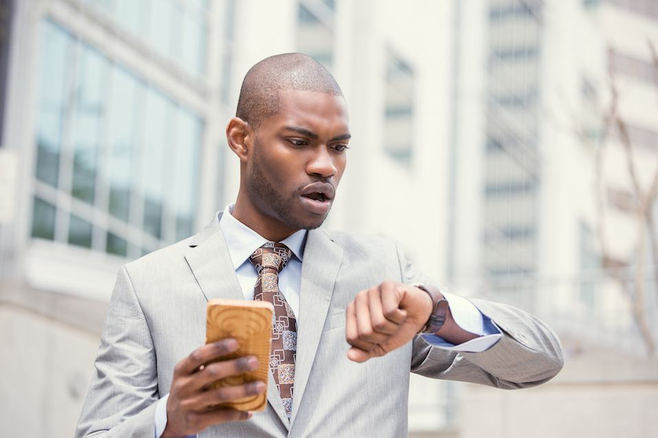 Stressed businessman looking at wrist watch