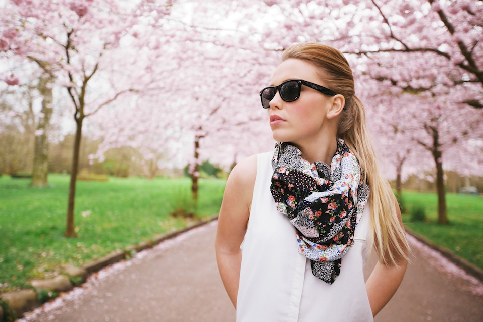 Stylish young woman posing at the spring blossom garden.