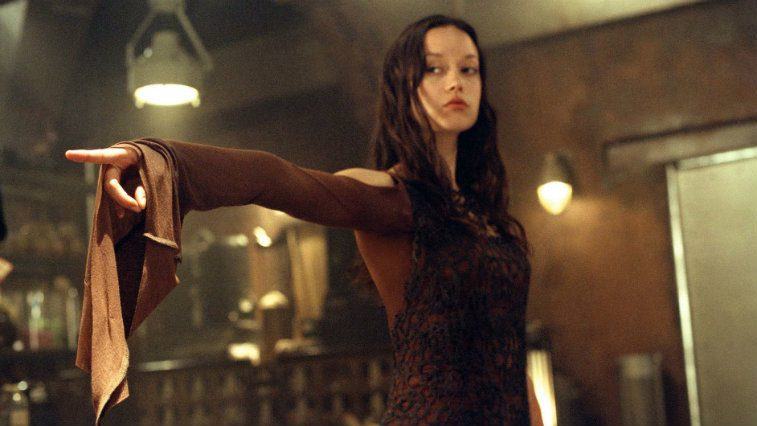 Summer Glau in Serenity standing defiantly looking off-camera with a hand pointed outward in a graceful pose.