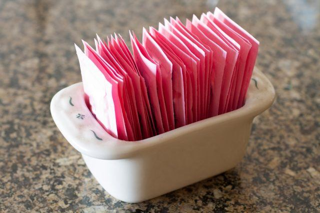 Container holding packets of artificial sweetener.