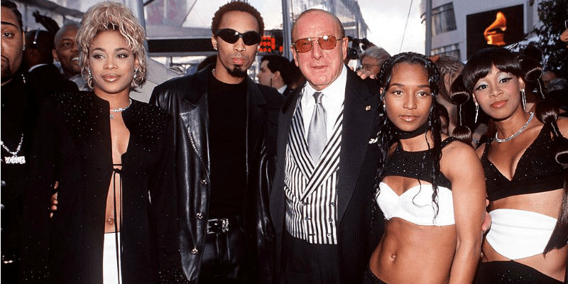 TLC is posing for a picture with Clive Davis on the red carpet.