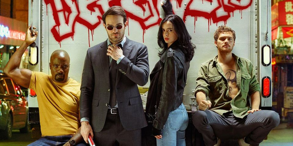 The Defenders sit on the back of a truck, posing for the camera in a press photo