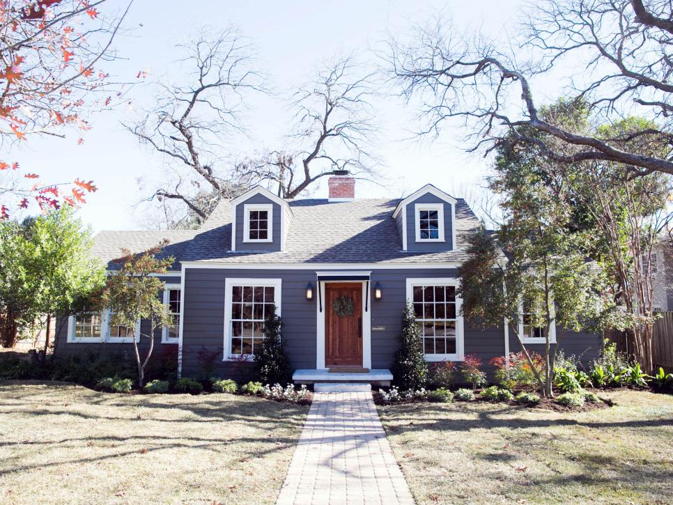 The exterior of this home features added dormers, a new front door, brick walkway, and fresh landscaping, as seen on Fixer Upper.