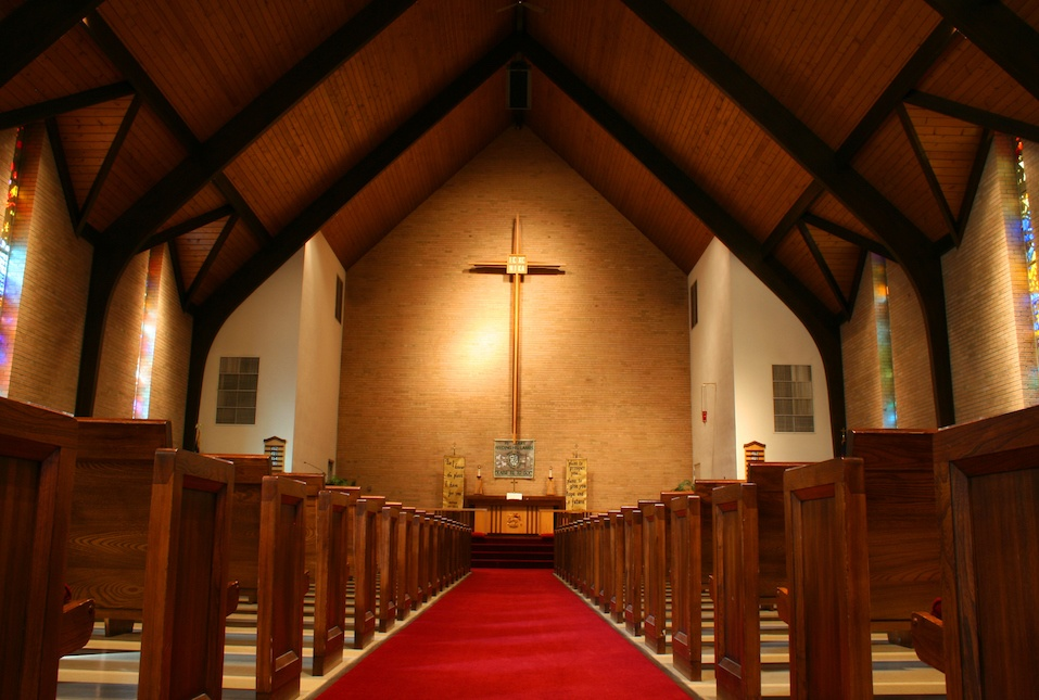 Inside of a large, modern church with pews and cross visible.