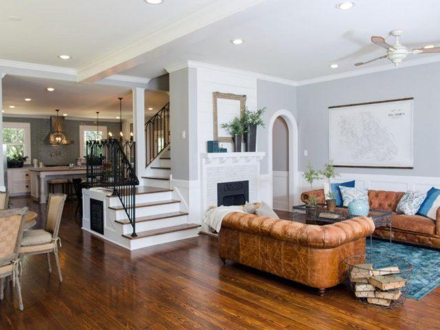 The living room in the Dansby home has been completely transformed. Some key elements are the removal of walls, raised ceilings, renovated fire place and wood flooring, as seen on HGTV's Fixer Upper.