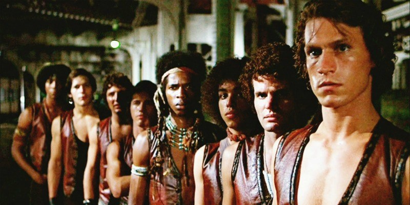 The gang, The Warriors are all lined up. dressed in brown leather vests with no shirt on