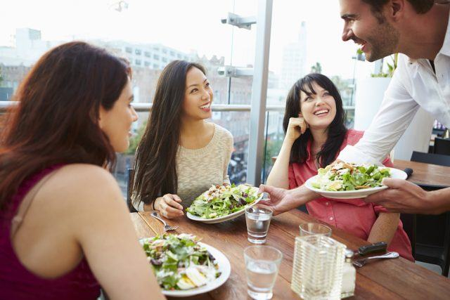 Female friends smiling and laughing at a restaurant
