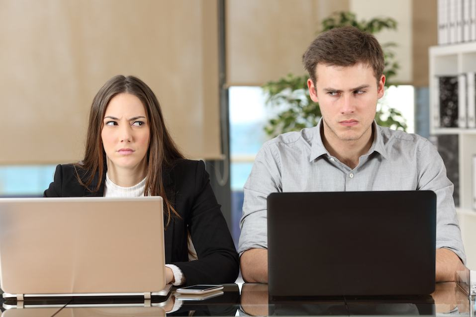 Two angry businesspeople sitting next to each other in an office