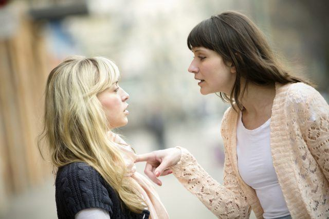 Two women arguing on the street.