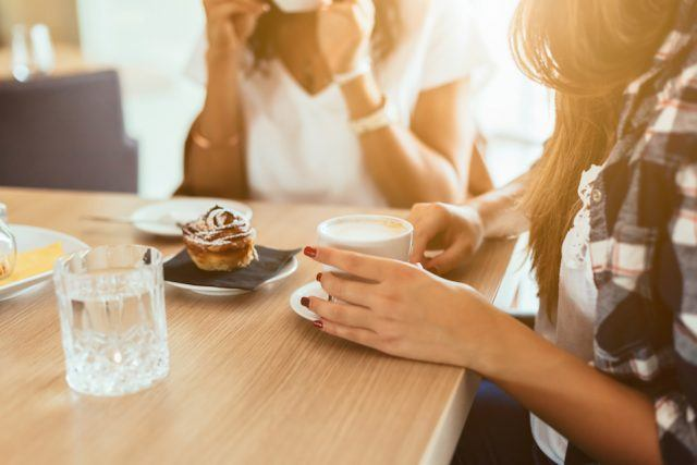 A woman speaks while the other is drinking coffee.