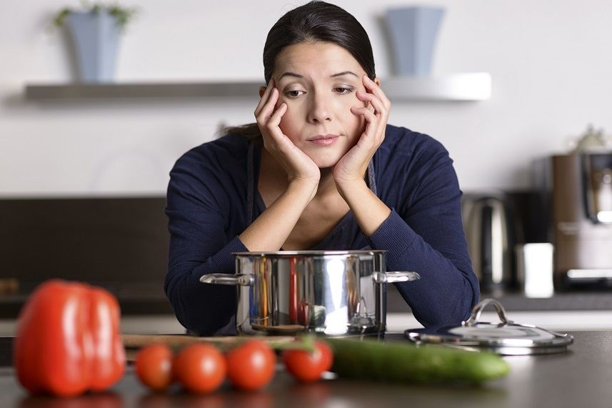 woman with her head in hands in the kitchen