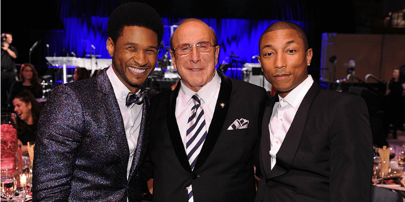 Usher, Clive Davis, and Pharrell Williams pose together for a picture.