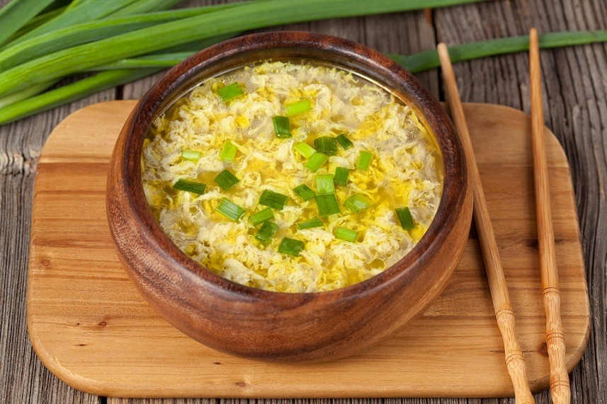 egg soup with broth in wooden bowl