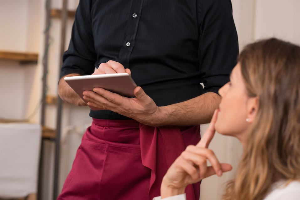 Young beautiful woman thinking of food to order in front of a waiter