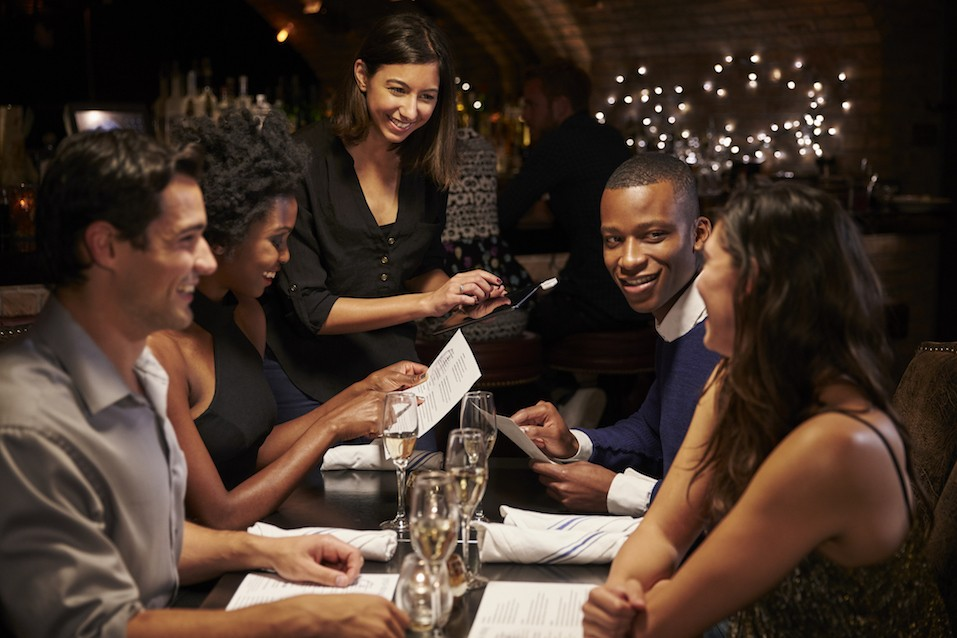 waitress takes order from table of four