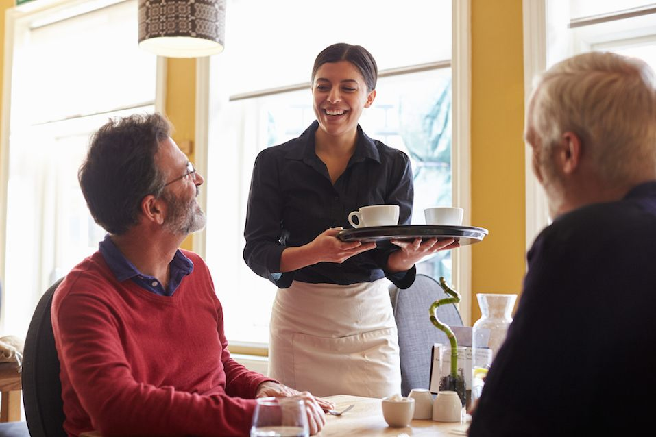 Waitress bringing coffees to a table