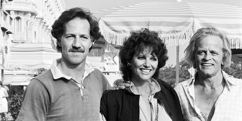 Werner Herzog, Claudia Cardinale, and Klaus Kinski have their arms around each other and are smiling.