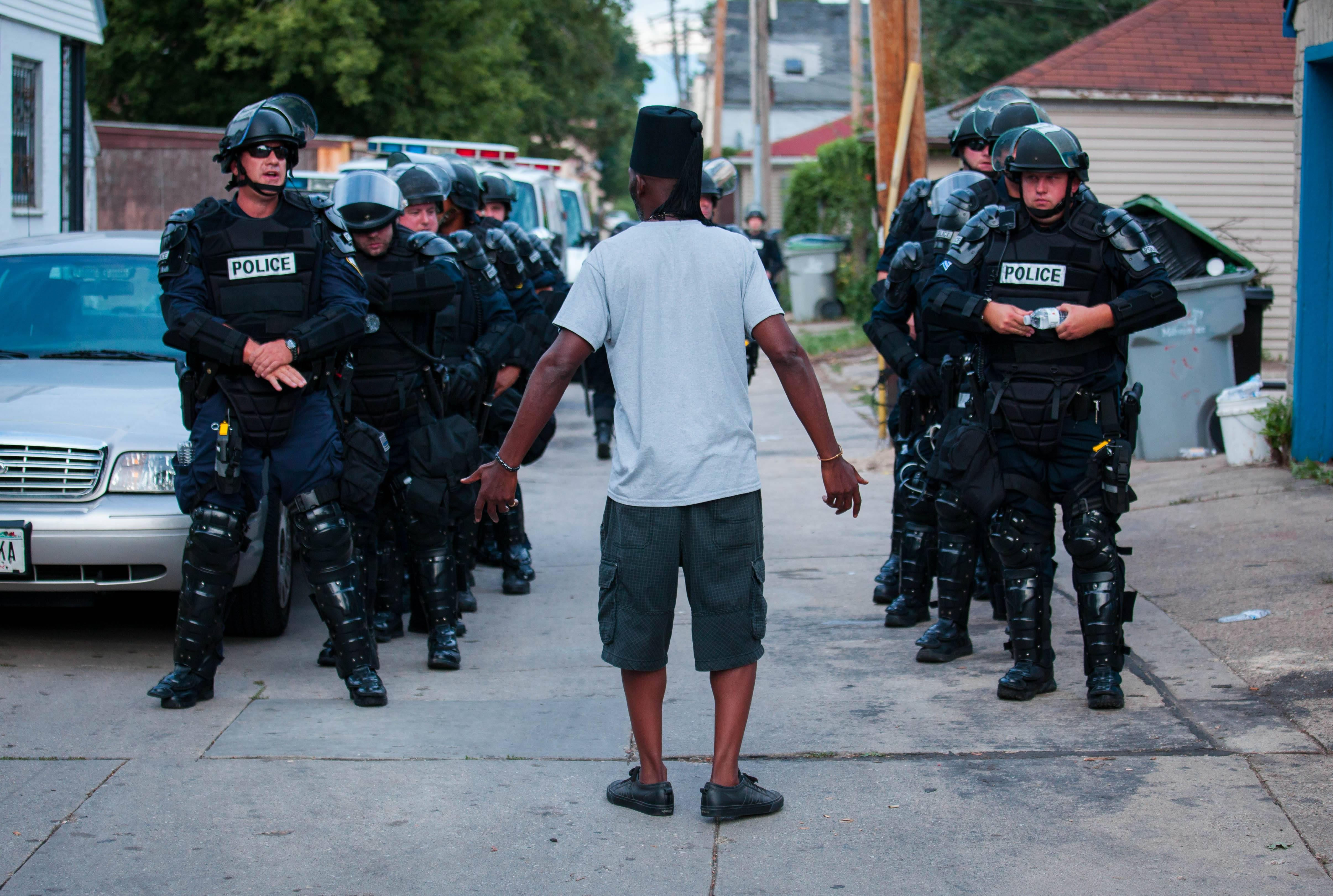 A man talks to police in riot gear