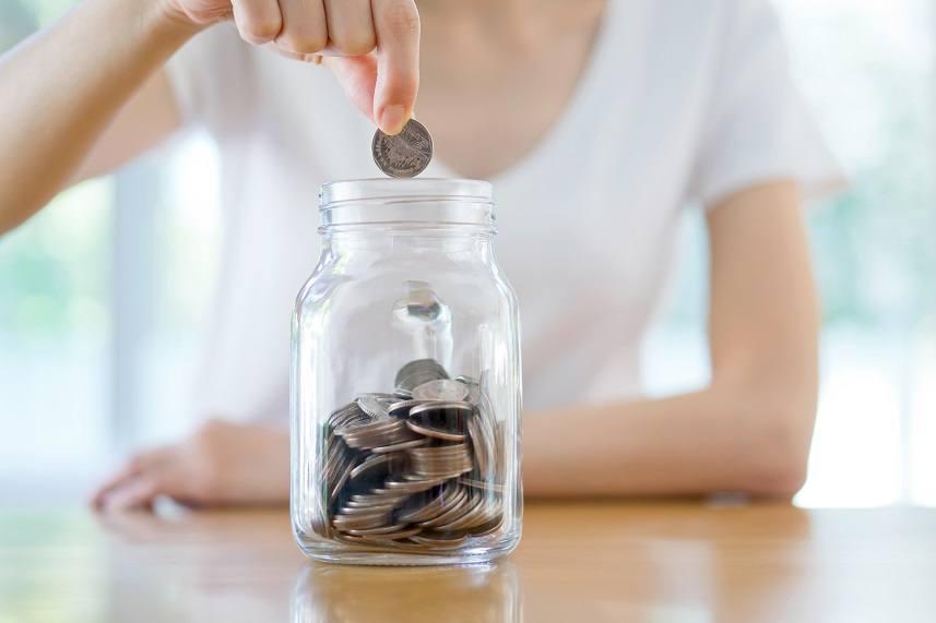 woman drops coins into a jar