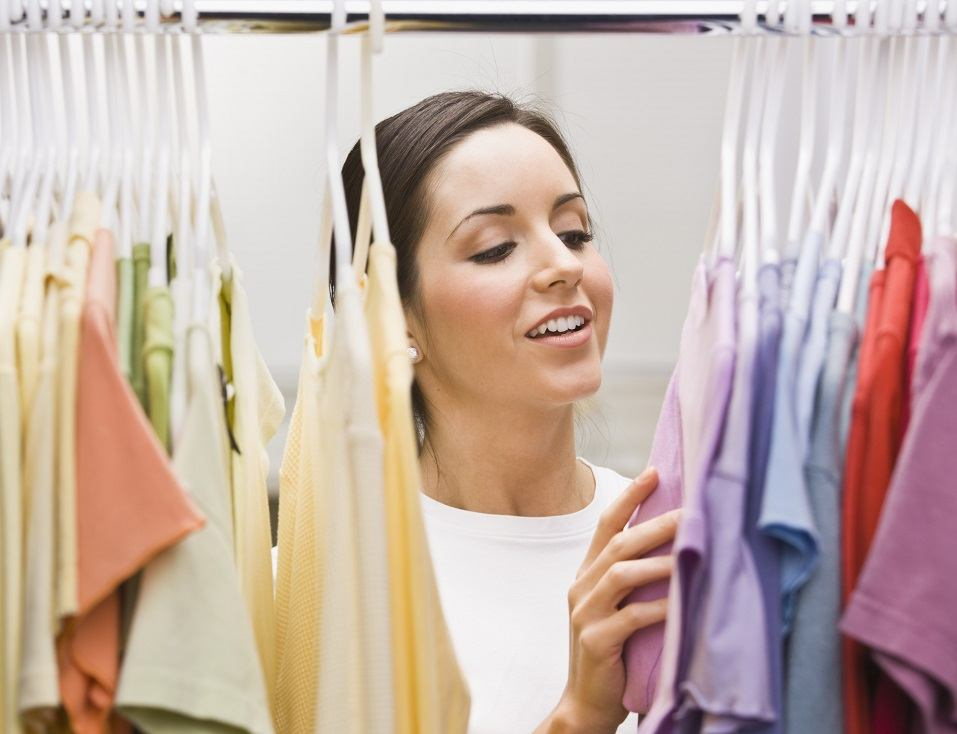 young female looking through a clothing closet