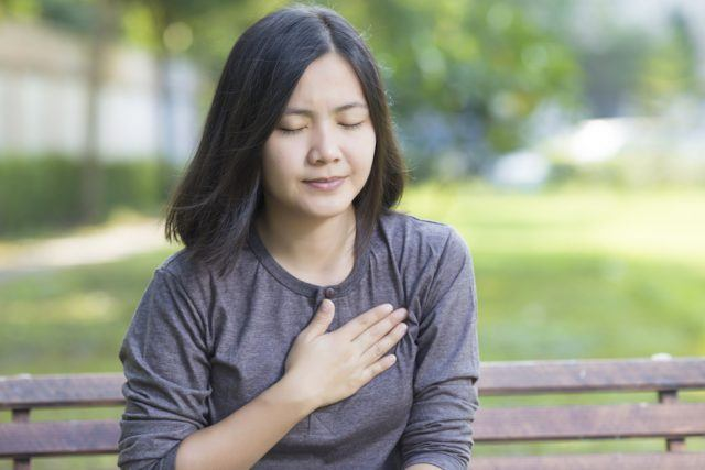 Woman touching her chest while sitting on a bench.