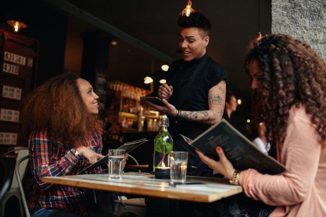 Two women sitting at cafe holding menu card giving an order to male waiter.