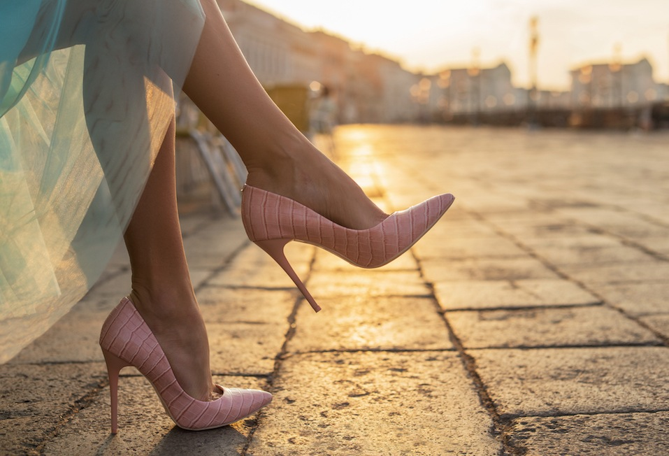 Woman in high heel shoes in city by sunrise