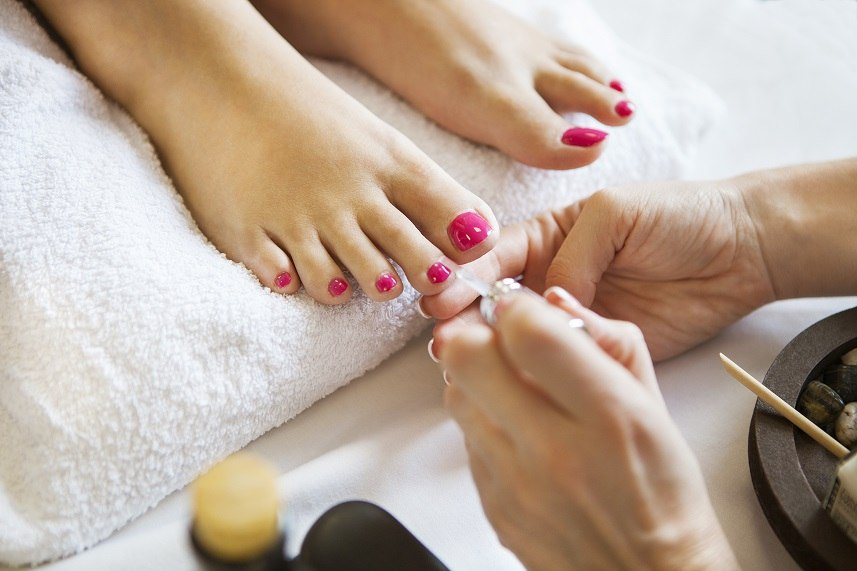 Woman in nail salon receiving pedicure
