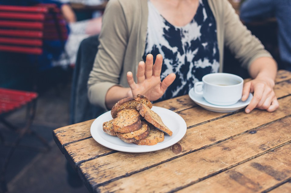 woman holding up her hand when offered a plate of toast