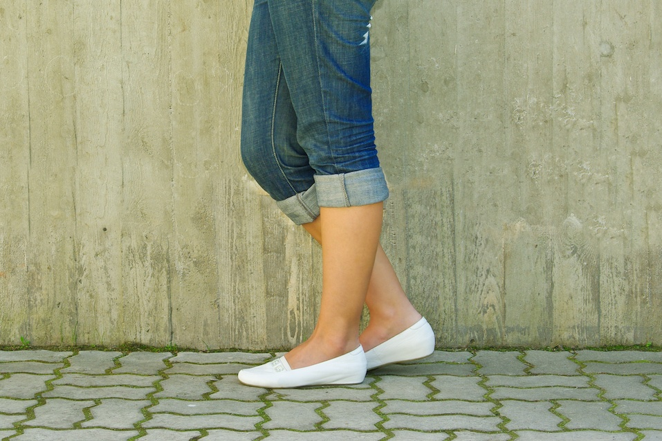 Woman's legs in jeans rolled up wearing white shoes