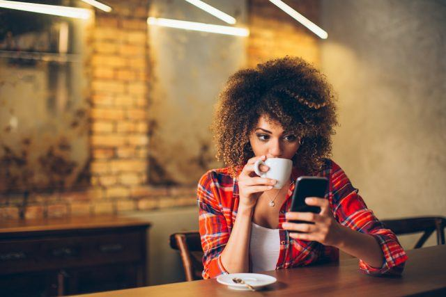 Young woman at cafe drinking coffee.