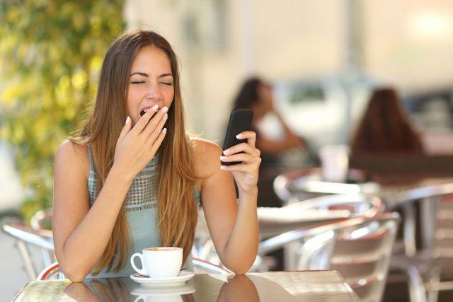 Woman yawning while is working on the phone at breakfast in a restaurant.