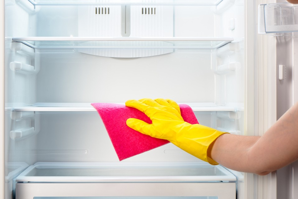 hand in yellow glove cleaning inside of fridge