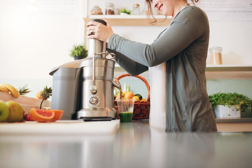 Young female bar employee making fruit juice
