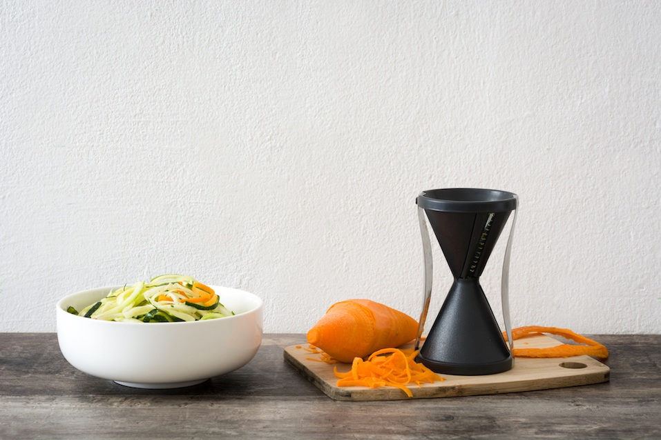 Zucchini and carrot noodles in a bowl, on wooden table