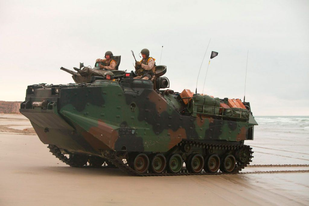 Marines drive an AAV7 Amphibious Assault Vehicle onto a beach.