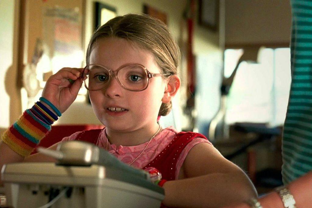 Abigail Breslin stands by the phone and touches her glasses in Little Miss Sunshine