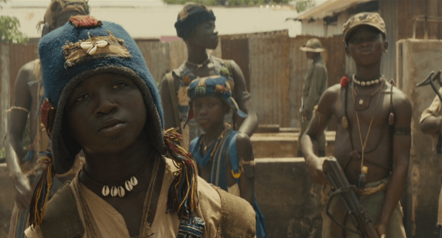 Agu stands looking defiant as child soldiers stand behind him holding weapons in a scene from 'Beasts of No Nation.'