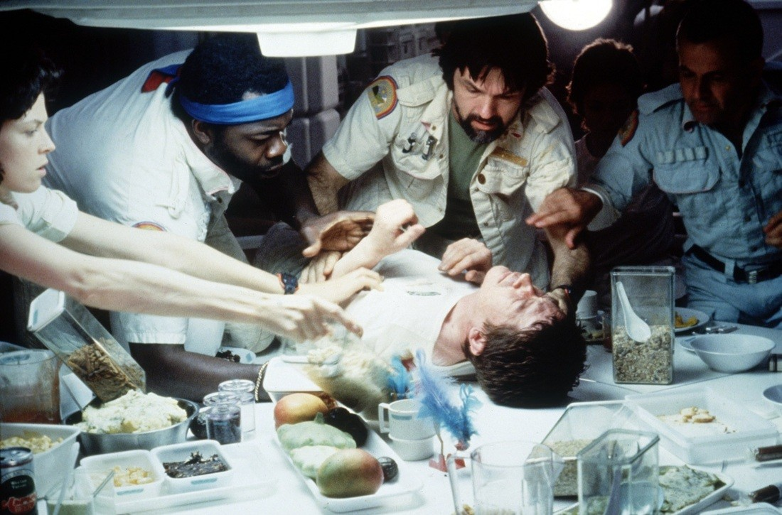 Actors gather around John Hurt, who's lying on a table wearing a white tshirt