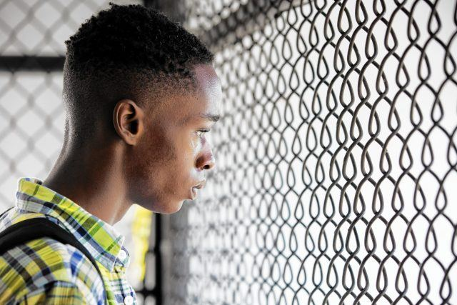 Chiron, as a teenager, stares through a fence in a scene from 'Moonlight.'