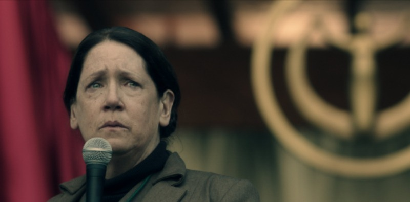 Aunt Lydia is on stage in front of a microphone with tears in her eyes.