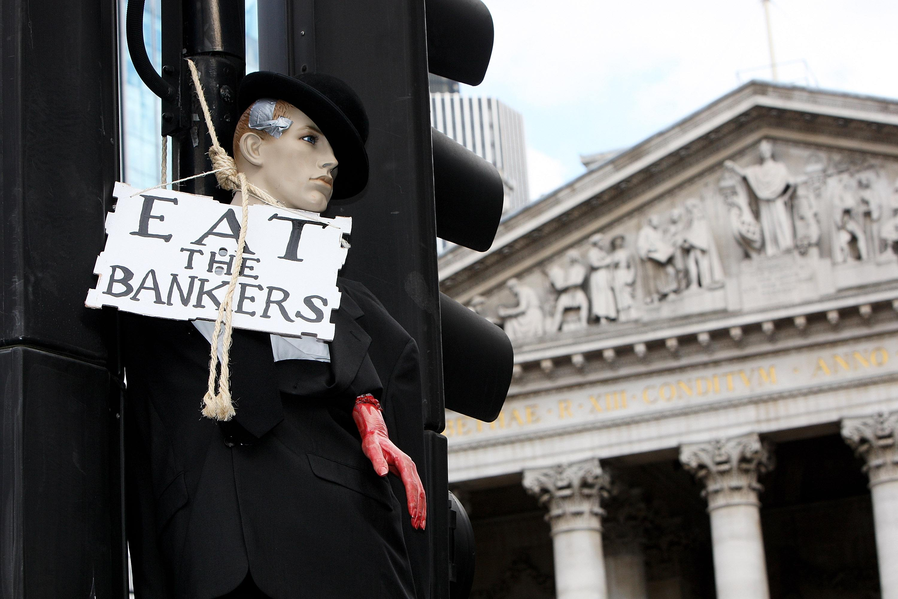 """A mannequin dressed as a banker hangs from a traffic light post with a sign that says """"eat the bankers."""""""